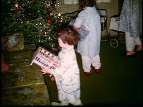 1960s HOME MOVIE high angle two small children playing with toy crib by Christmas tree in living room