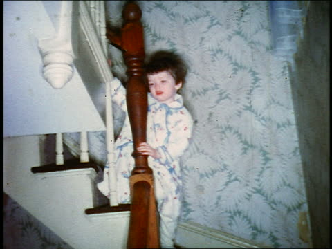 1960s home movie low angle small girl in pajamas slowly walking down stairs on christmas morning - 1960 stock videos and b-roll footage