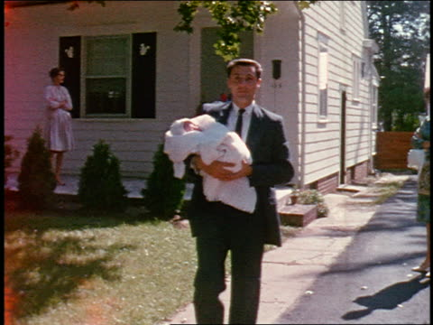 1960s home movie man in suit holding newborn walking toward camera outdoors / close up baby's face - home movie stock videos & royalty-free footage