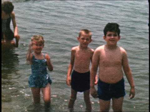 1960s home movie portrait  three children in swimsuits standing in lake / girl waves at camera - family waving stock videos & royalty-free footage