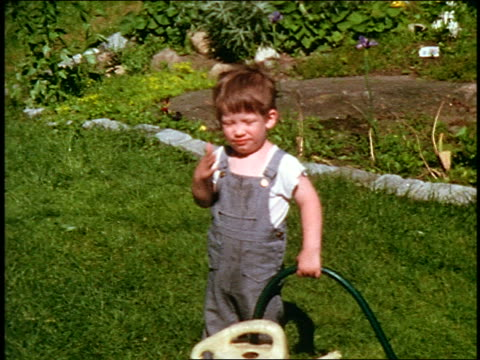 1960s HOME MOVIE small boy in overalls holding hose standing in grass + rubbing eyes