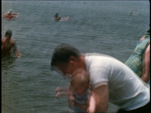 1960s HOME MOVIE tilt down man holding baby girl in swimsuit / he puts her down in water on beach