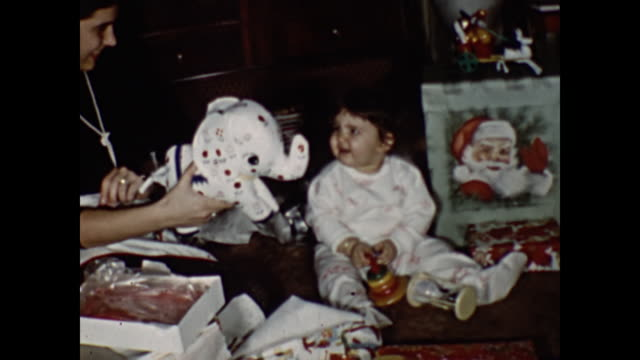 1960s Home Movie - Toddler girl opening gifts by Christmas tree
