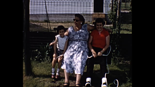 1960s home movie - woman and daughters on swing - single mother stock videos & royalty-free footage