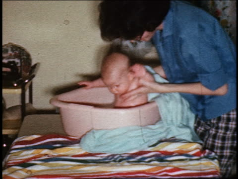 vidéos et rushes de 1960s home movie woman bathing baby in washtub on table - 1960