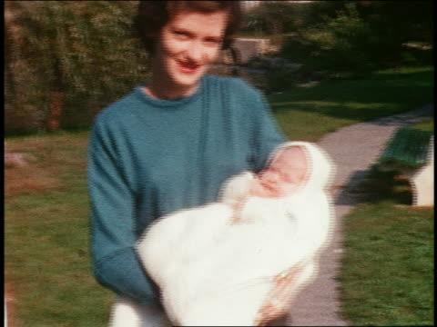 1960s home movie woman holding newborn walking toward camera outdoors / close up baby - 帶 握住 個影片檔及 b 捲影像