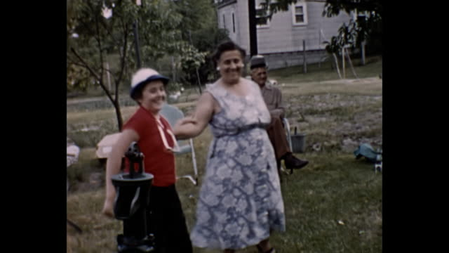 1960s home movie - women dancing at family picnic - older woman fun stock-videos und b-roll-filmmaterial