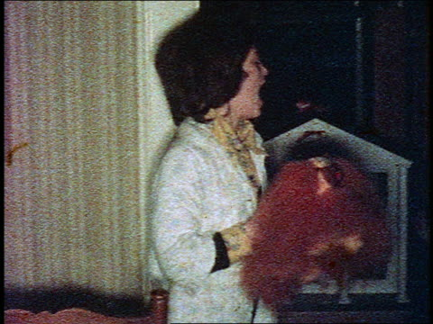 1960s HOME MOVIE young girl in pajamas shaking stuffed dog then posing by dollhouse indoors