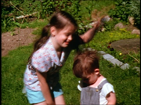 1960s home movie young girl + small boy standing in grass / girl waves then waves boy's hand at cam - dungarees stock videos and b-roll footage