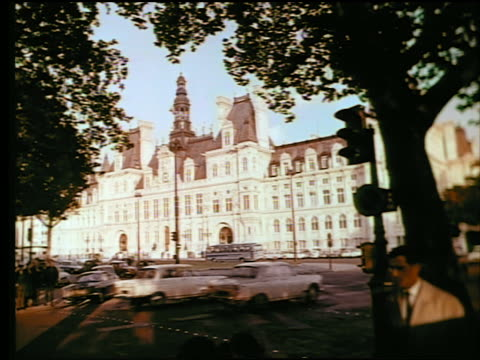 1960s Hotel de Ville / traffic, man walking + silhouetted tree in foreground / Paris, France