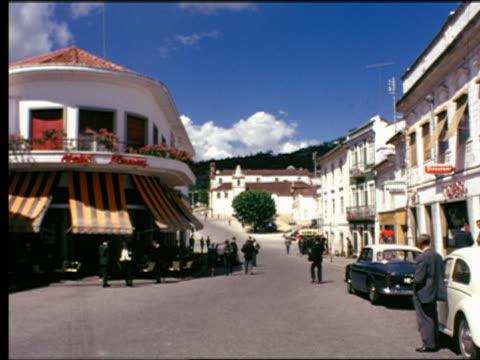 vidéos et rushes de 1960s hotel with outdoor cafe + people on village street / portugal - groupe moyen d'objets