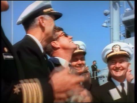 1960s john kennedy + naval officers looking up smiling / watching missile / crossed fingers in foreground - john f. kennedy myndighetsroll bildbanksvideor och videomaterial från bakom kulisserna