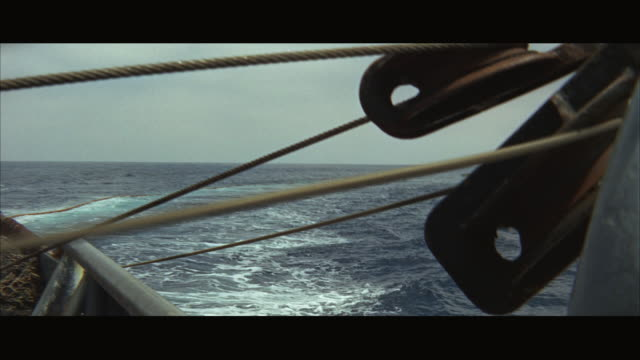 vídeos de stock e filmes b-roll de 1960s ms pov large fishing boat, as net plays out over stern of boat into ocean - rede de pesca comercial