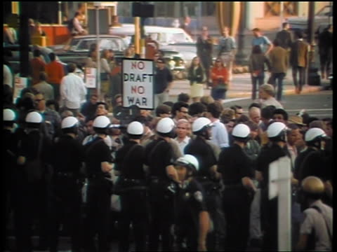 1960s line of policemen blocking crowd holding no draft no war sign at peace demonstration - peace demonstration stock videos and b-roll footage
