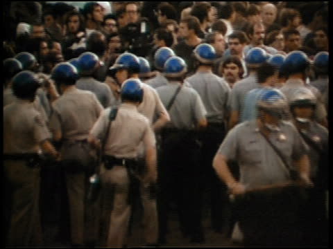 1960s line of policemen in helmets blocking crowd during peace demonstration - peace demonstration stock videos and b-roll footage