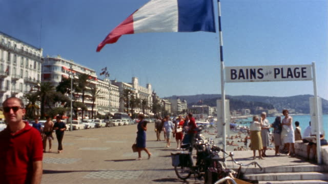 vídeos de stock, filmes e b-roll de 1960s long shot people on beach with french flag in foreground / cannes, france - cannes