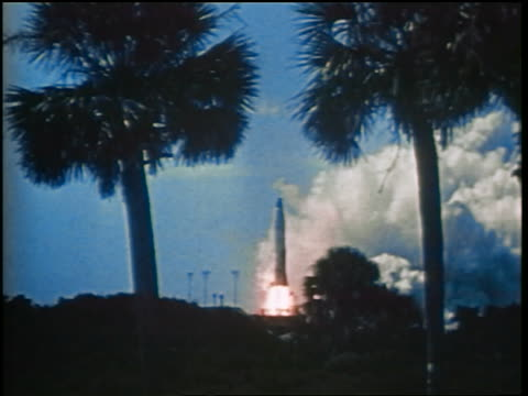 1960s long shot tilt up missile blasting off with two palm trees in foreground / Cold War / documentary