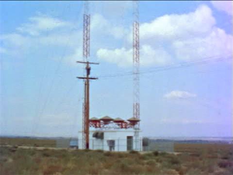 vídeos de stock, filmes e b-roll de 1960s long shot tilt up radio tower outdoors / educational - torre de comunicações