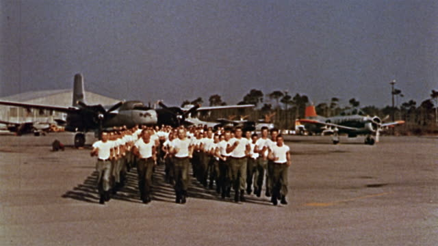 1960s long shot us soldiers running towards cam in rows with planes in background - army exercise stock videos and b-roll footage