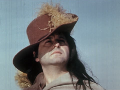 1960s low angle close up reenactment man wearing large french cavalier hat with plume / glancing from side to side - stilrichtung des 17. jahrhunderts stock-videos und b-roll-filmmaterial