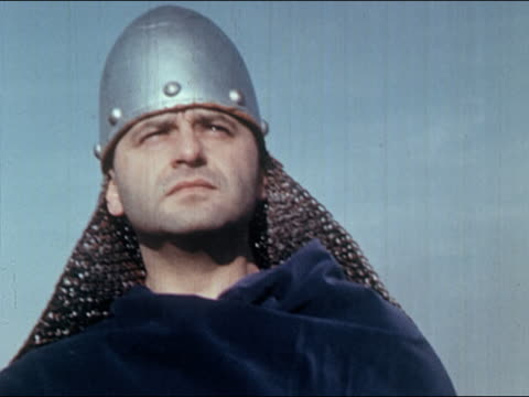 vídeos de stock e filmes b-roll de 1960s low angle close up reenactment saxon soldier wearing metal helmet with chain mail glancing from side to side - olhar de lado