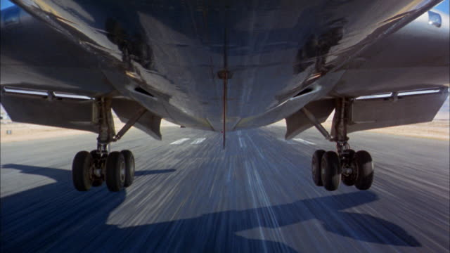 1960s low angle close up wheels touching down on runway during 707 jet plane landing - touching stock-videos und b-roll-filmmaterial