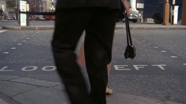 1960s low angle close up woman in mini-skirt waiting to cross street / woman and man w/umbrella crossing street