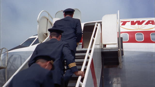 1960s low angle medium shot airline pilots and flight attendants running up stairs + boarding twa airplane - pilot stock videos & royalty-free footage