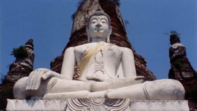 1960s low angle medium shot Buddha statue