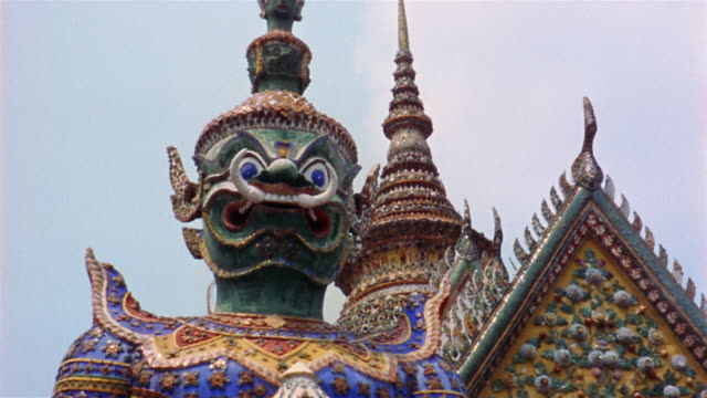 1960s low angle medium shot detail of statue and Thai temple  / Thailand