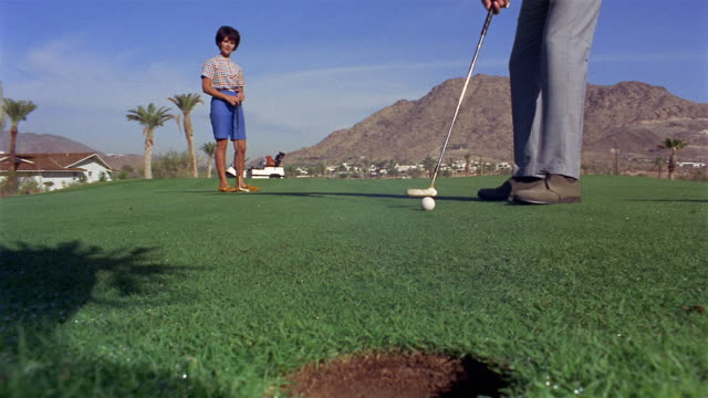 1960s low angle medium shot man putting golf ball into hole - golf club stock videos and b-roll footage