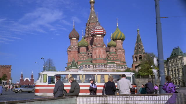 1960s low angle medium shot traffic in front of St. Basil's Cathedral / Kremlin, Moscow