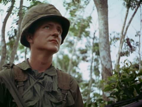 1960s low angle medium shot us soldier wearing helmet and looking around / vietnam - 若い男性だけ点の映像素材/bロール