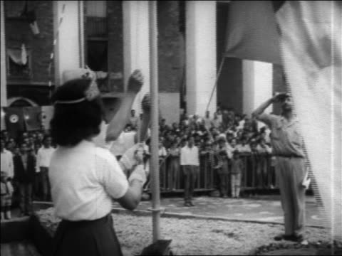 B/W 1960s low angle tilt up girl raising Algerian national flag on flagpole / Algeria / educational