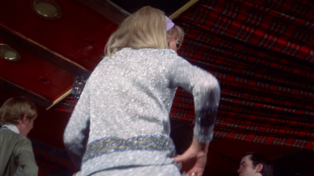 1960s low angle tilt up medium shot blonde woman in sparkling silver outfit dancing on dance floor