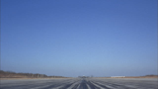 vídeos y material grabado en eventos de stock de 1960s low angle wide shot 707 jet plane moving toward cam on runway and taking off over cam - air vehicle