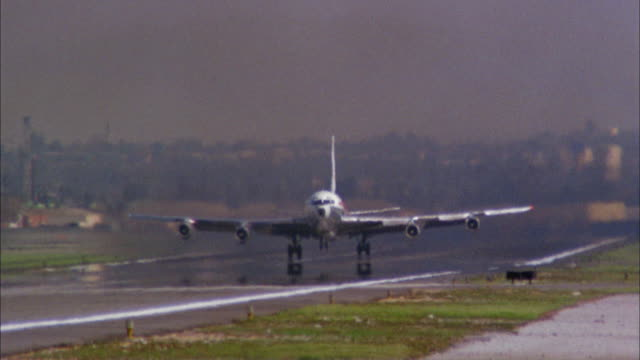 1960s low angle wide shot 707 jet plane taking off and landing gear folding in