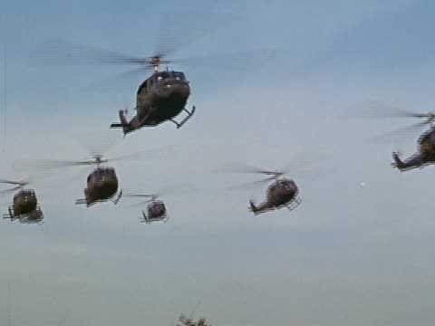 1960s low angle wide shot fleet of bell uh1 iroquois helicopters flying through the air / vietnam - military helicopter stock videos & royalty-free footage