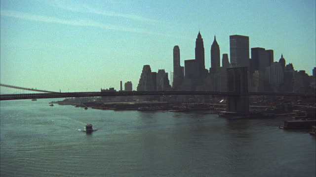 vídeos de stock, filmes e b-roll de 1960s ws ha lower manhattan skyline with ferryboat by brooklyn bridge / new york city, usa - baixo manhattan