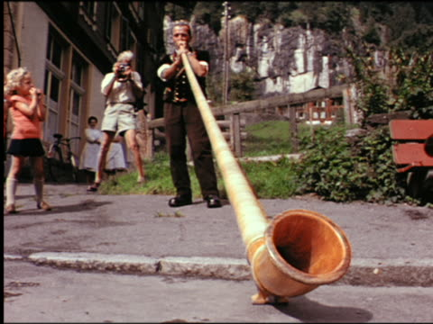 1960s man blowing alpenhorn with man taking photograph with camera in background / switzerland - 1960 stock-videos und b-roll-filmmaterial
