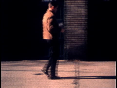 1960s ws man carrying objects, dropping one and bending from the knees to carefully pick it up / united states - menschliches knie stock-videos und b-roll-filmmaterial