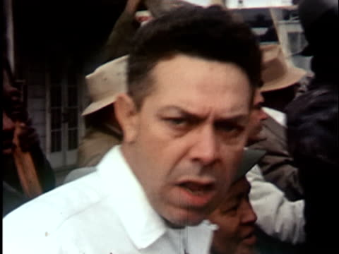 CU 1960s Man in angry mob turning and yelling aggressively at camera, California / USA