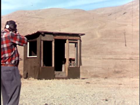 vidéos et rushes de ms 1960s man in gas mask firing tear gas canister at shack in desert landscape, california / usa - cabane structure bâtie