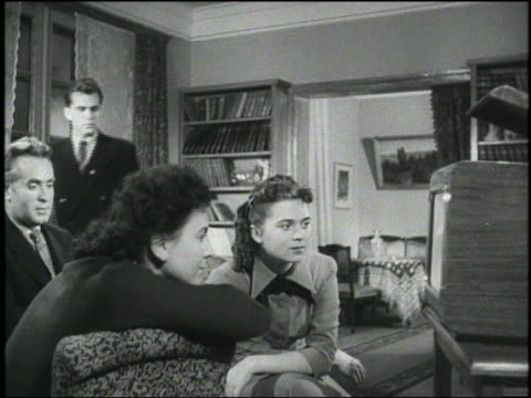b/w 1960s man joins other man + two women watching television in living room - black and white stock videos & royalty-free footage