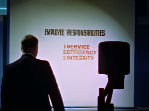 1960s man pointing to transparency projected on wall + talking in seminar / educational - overhead projector stock videos & royalty-free footage