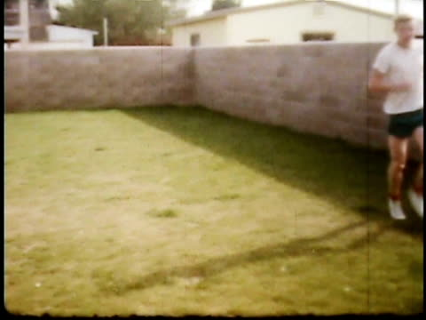 1960s ws pan man running laps in small back yard, accompanied by dog / lompoc, california, usa - 1960 stock-videos und b-roll-filmmaterial