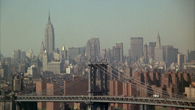 1960s ws ha manhattan skyline with manhattan bridge in foreground / new york city, usa - 1960 1969 stock-videos und b-roll-filmmaterial