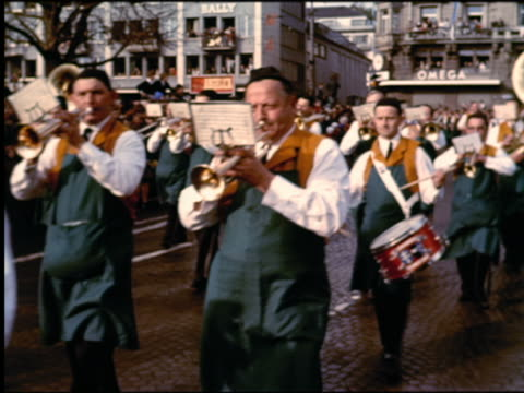1960s marching band passing camera on street in parade / zurich, switzerland - marching band stock videos and b-roll footage