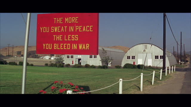 1960s WS Marine barracks with sign reading: the more you sweat in peace the less you bleed in war
