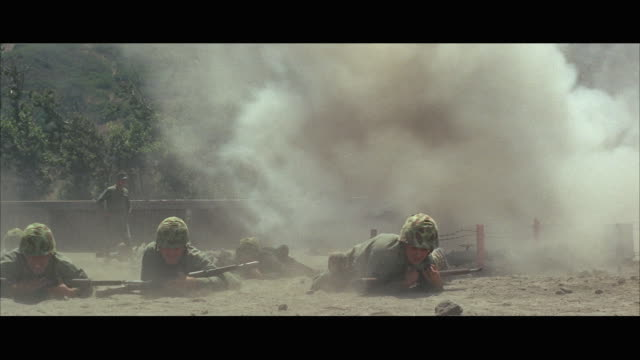 stockvideo's en b-roll-footage met 1960s ws marines crawling across field under fire - militaire training